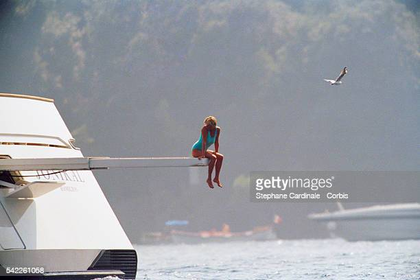 Lady Diana, Princess of Wales, sitting on the diving board of Mohammed Al Fayed's private yacht 'Jonikal' as a seagull flies overhead.