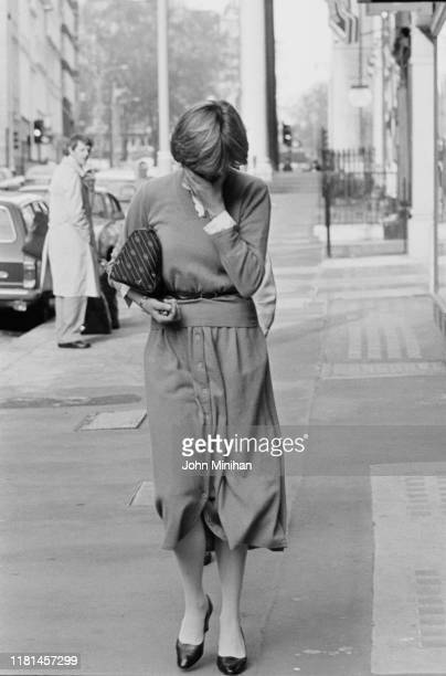 Lady Diana Spencer covers her face as she walk on a street in London UK 17th November 1980 she is wearing cardigan and midi skirts buttoned on front