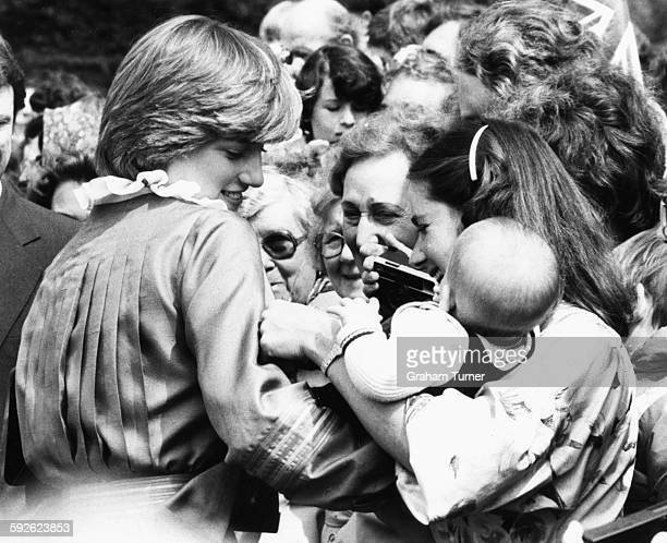 Lady Diana Spencer fiance of Prince Charles holding a baby as she greets the crowds of onlookers during the opening of the Mountbatten Exhibition at...