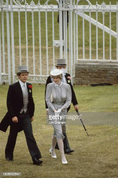 Lady Diana Spencer , fiancee of Charles, Prince of Wales, wearing a grey check belted dress with a white John Boyd hat, with unspecified men in...