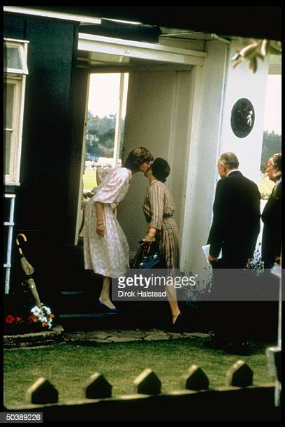 Lady Diana Spencer kissing her motherinlaw to be Queen Elizabeth II in greeting before going to watch fiance Prince Charles play polo