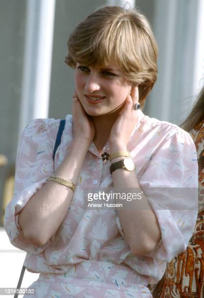 Lady Diana Spencer, wearing a pink patterned dress, two watches and a gold bracelet which were birthday presents from Prince Charles, attends the...