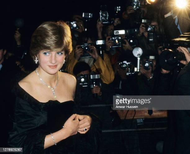 Lady Diana Spencer, wearing a strapless black taffeta dress designed by David and Elizabeth Emanuel, attends a fundraising concert and reception at...