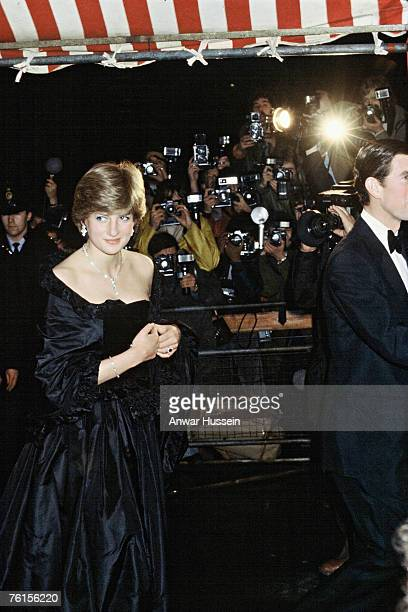 Lady Diana Spencer arrives in a revealing David Emanuel black dress for her first official engagement with Prince Charles at a fundraising concert at...