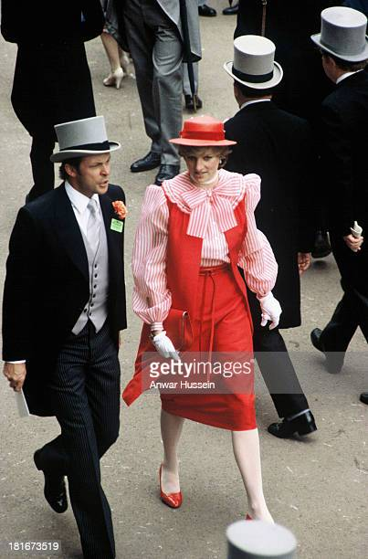 Lady Diana Spencer, wearing an outfit by Bellville Sassoon and red heels, is accompanied by her bodyguard Graham Smith, as she attends Royal Ascot...
