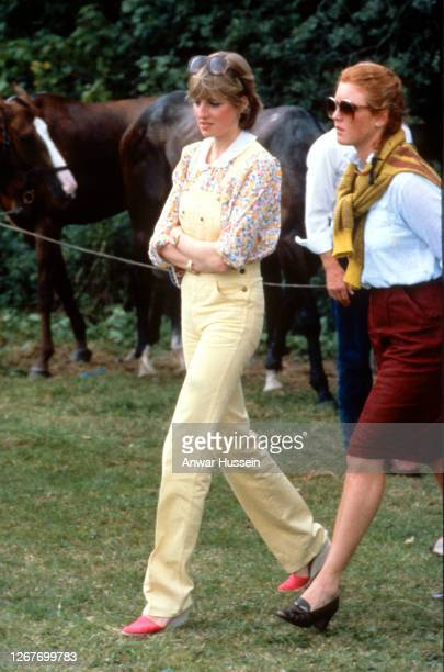 Lady Diana Spencer, wearing yellow dungarees with a floral blouse and red wedges, and Sarah Ferguson attend a polo match at Cowdray Park Polo Club in...