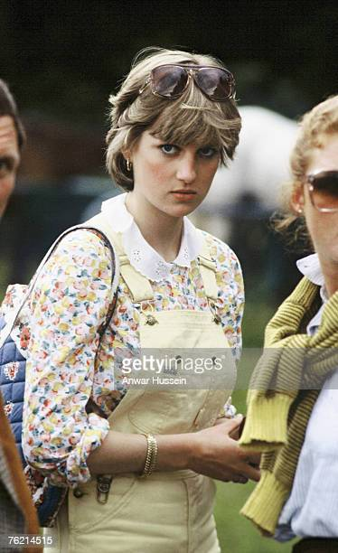 Lady Diana Spencer, wearing yellow dungarees with a floral blouse and red wedges, attends a polo match at Cowdray Park Polo Club on July 12, 1981 in...