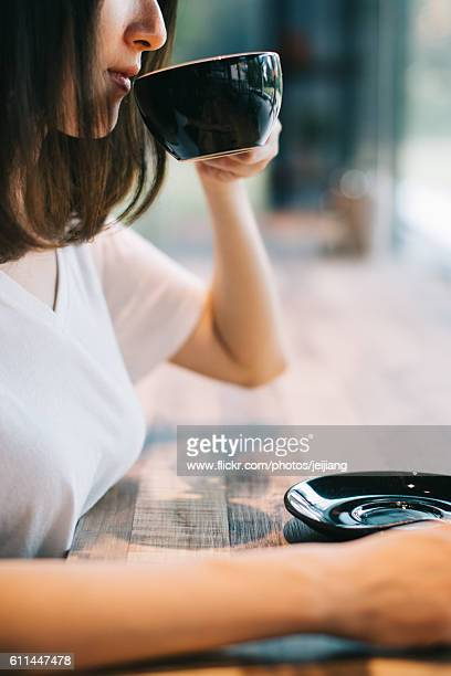 A Lady Drinking Her Cappuccino from a Black Coffee Cup