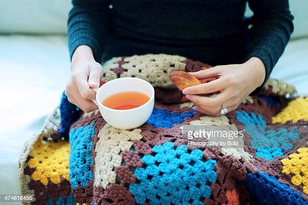 Lady elegant hold Madeleine cake with tea sitting