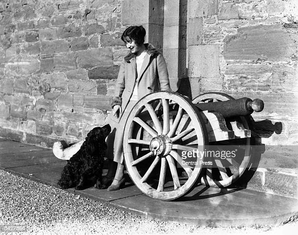 Lady Elizabeth BowesLyon leans against a gun carriage as she plays with a dog at her childhood home Glamis Castle Angus