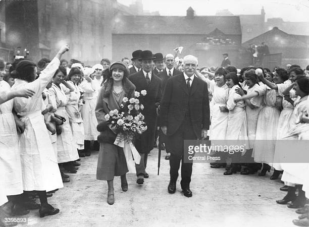 Lady Elizabeth BowesLyon walking through a cheering crowd in the courtyard of an Edinburgh factory followed by George Duke of York shortly before...