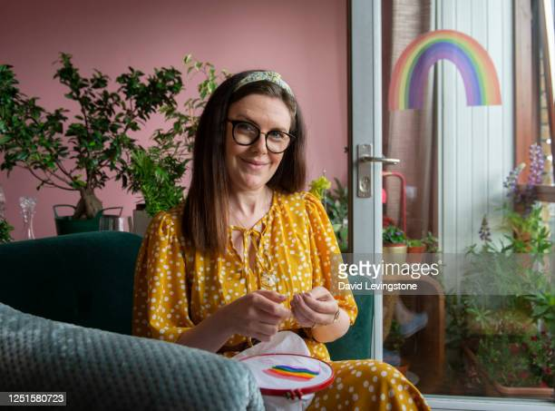 lady embroidering a rainbow in support of lgbtqi+ pride parade at home - needlecraft stock pictures, royalty-free photos & images