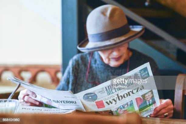 A lady enjoys reading a local newspaper in one of Krakow's city center cafe On Thursday April 13 in Krakow Poland