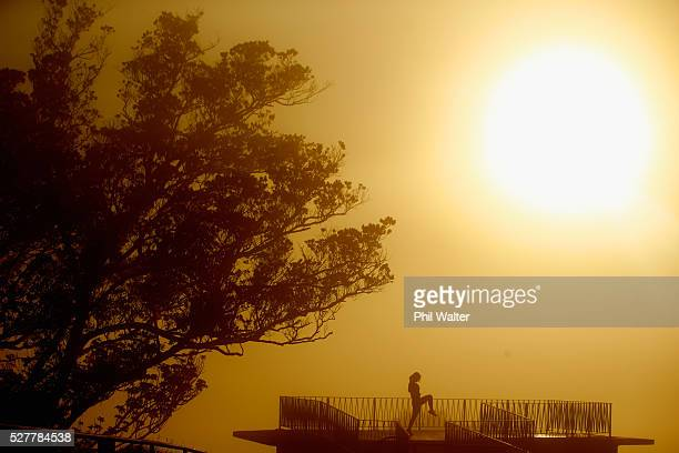 A lady exersises on the summit of Mt Eden as the sun struggles to shine through a blanket of fog over Auckland City on May 4 2016 in Auckland New...