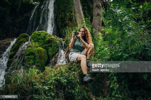 lady explorer sitting by the waterfall - ecoturismo foto e immagini stock