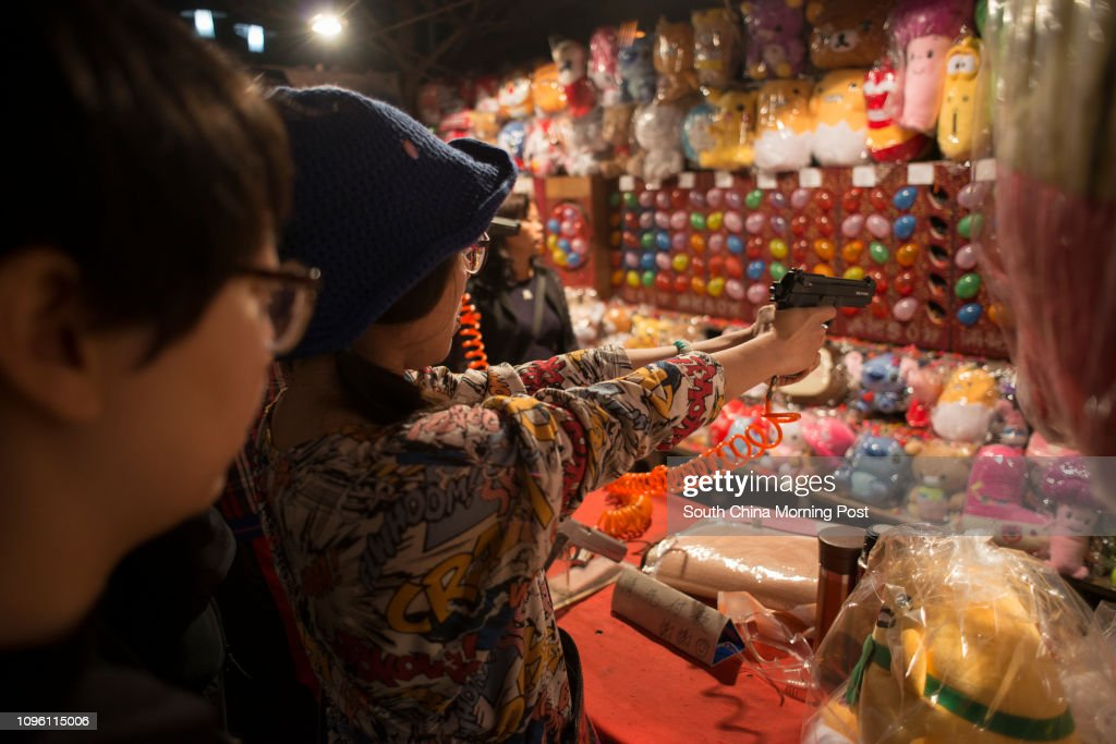 A lady fires a bb gun at a target, at the Tainan Flower