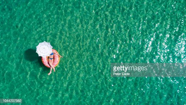 lady floating in the sea in a rubber ring, holding umbrella - auf dem wasser treiben stock-fotos und bilder