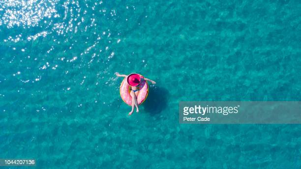 lady floating in the sea in a rubber ring, wearing large hat - rubber ring stock pictures, royalty-free photos & images