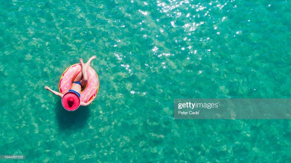 Lady floating in the sea in a rubber ring, wearing large hat : Stock Photo