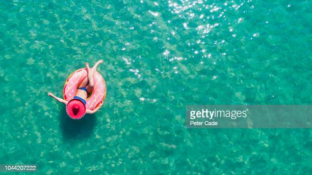 lady floating in the sea in a rubber ring, wearing large hat - vacanze foto e immagini stock