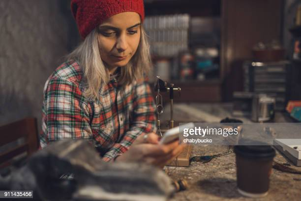 Lady fly fisher using smartphone