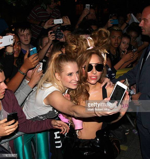 Lady Gaga interacts with fans as she leaves the Langham Hotel on August 27 2013 in London England