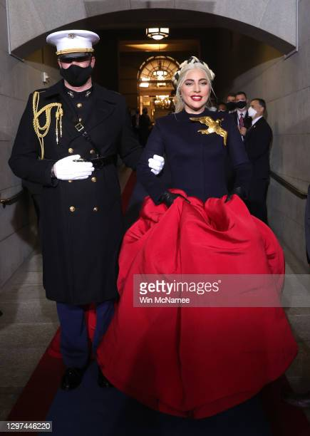 Lady Gaga is escorted by U.S. Marine escort Capt. Evan Campbell to sing the National Anthem at the inauguration of U.S. President-elect Joe Biden on...