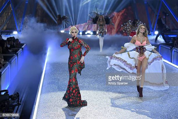 Lady Gaga performs as Flavia Lucini walks the runay during the Victoria's Secret Fashion Show on November 30 2016 in Paris France