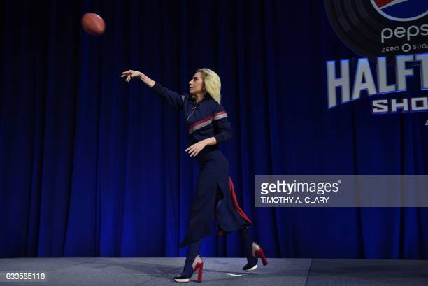 TOPSHOT Lady Gaga throws a football as she meets with the press during the Super Bowl LI Pepsi Zero Sugar Halftime Show Press Conference at the...