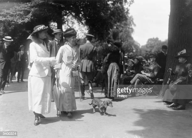 Lady Georgina Agar and Lady Ernest St Maur walking with their dachshund through Hyde Park London
