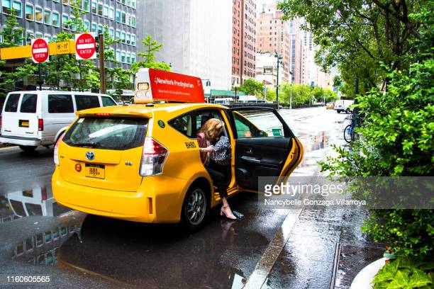 lady getting off from a yellow taxi during a rainy day in new york city - nancybelle villarroya stock photos and pictures