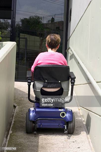 A lady going down a ramp in a motorized wheelchair