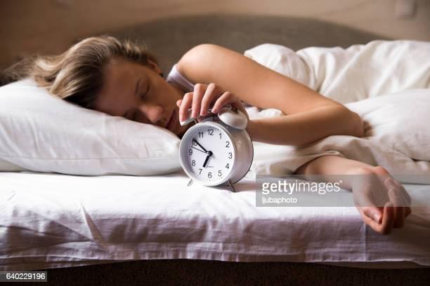 Lady has woken up by an alarm clock. eyes closed