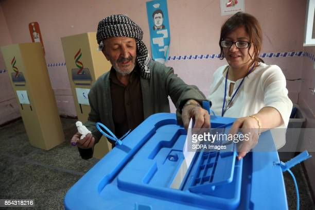A lady helps an old man to cast his vote at the voting station September 25 2017 is a historic day for Kurdish people around the world as many...