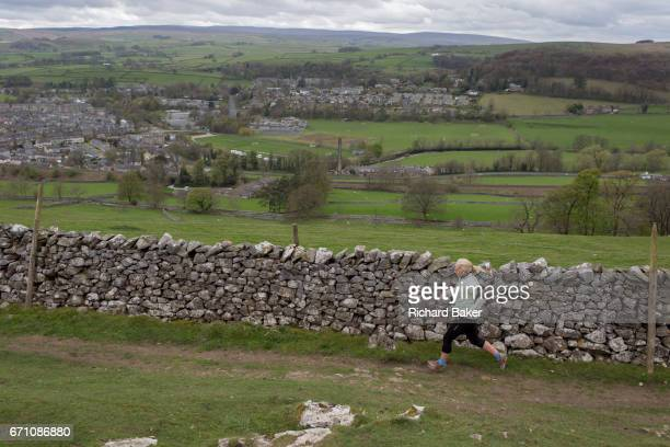 A lady hill runner jogs along a dry stone wall on a footpath above the town of Settle on 13th April 2017 Yorkshire England