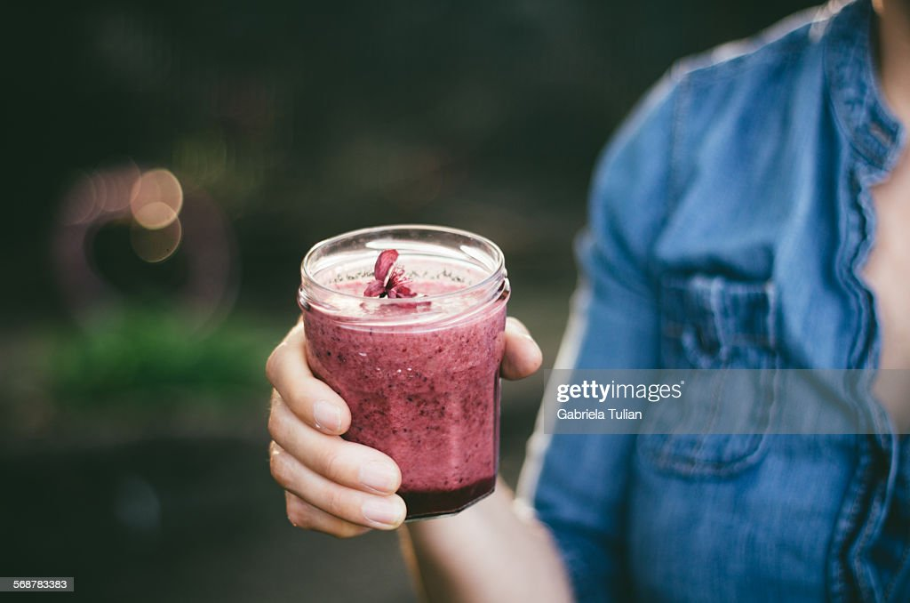 Lady holding a fresh berries smoothie : Stock Photo