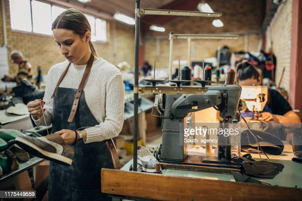 lady holding a leather shoe in shoe factory - shoe factory stock pictures, royalty-free photos & images
