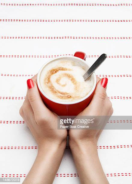 lady holding red mug of hot cappuccino