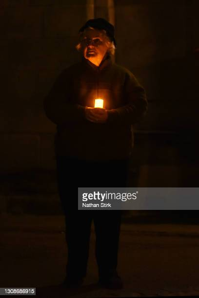Lady holds a candle during a minutes silence outside Lichfield Cathedral on March 23, 2021 in Lichfield, England. Marie Curie Cancer Charity has...