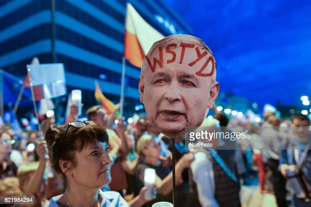 A lady holds an image of PiS Chairman Jaroslaw Kaczynski's face withthe word 'Shame' written on his forehead during an antigovernment candlelit vigil...
