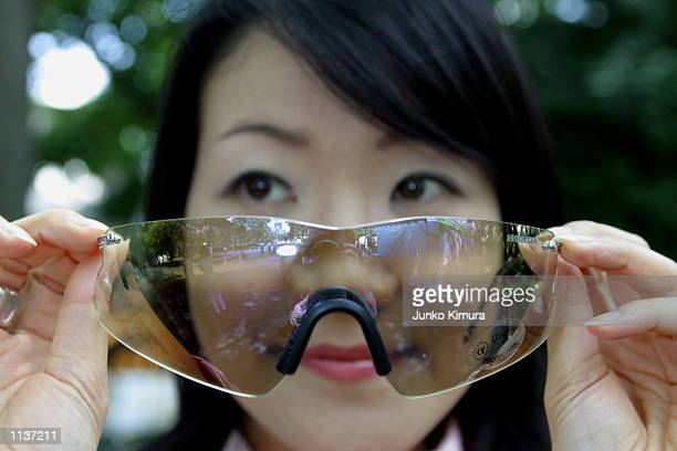 A lady holds Honda's new glasses Beam Free Mirror Glassesat Honda's press conference July 22 in Tokyo Japan In order to give more comfort to riders...
