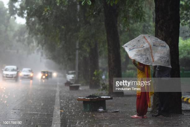 Lady holds PP sack to protect herself from rains near India Gate on July 13, 2018 in New Delhi, India. The national capital witnessed heavy rains in...