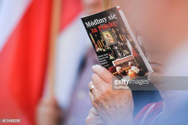 A lady holds 'We pray for Poland' book during the 87th monthly anniversary of Smolesk's catastrophe outside Wawel Castle in Krakow President Lech...