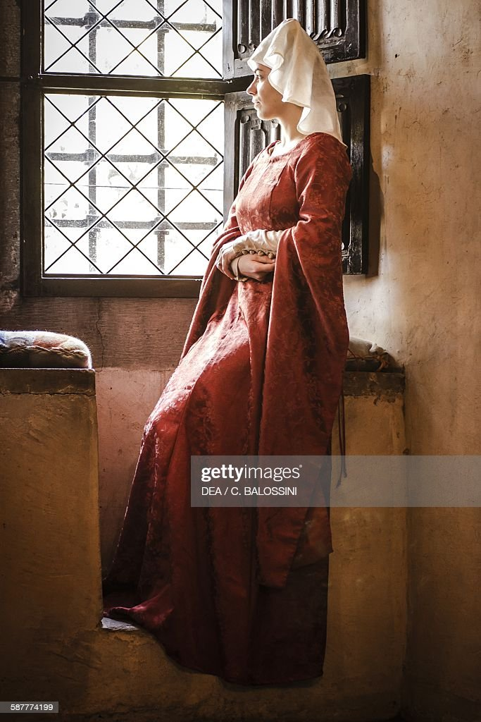 Lady in a Savoy court at a castle window, wearing a damask