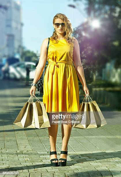 lady in a yellow dress with shopping bags - gelbes kleid stock-fotos und bilder