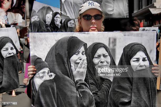 Lady in an anti war protest down Broadway in Manhattan NYC holding a poster of Islamic women mourning the death of their families in IRAQ/AFGHANISTAN.