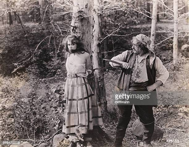 Lady In Distressbound to a tree being threatened by a desperado holding a knife