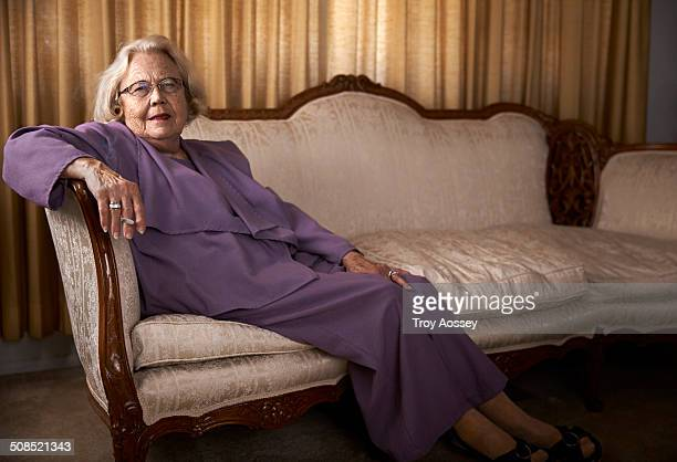 lady in purple suit sitting on couch and smoking. - tempe arizona stock pictures, royalty-free photos & images