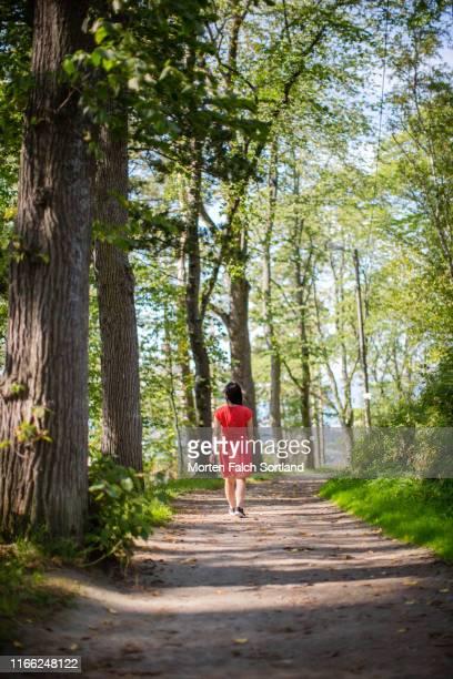 lady in red dress enjoying nature in trondheim, norway - menselijke rug stockfoto's en -beelden