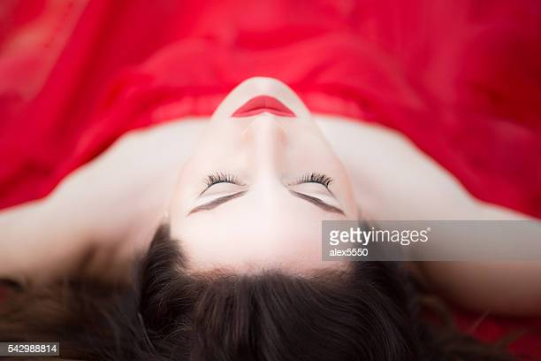 Lady in Red Dress Laying Down Eyes Closed Relaxed Sleeping